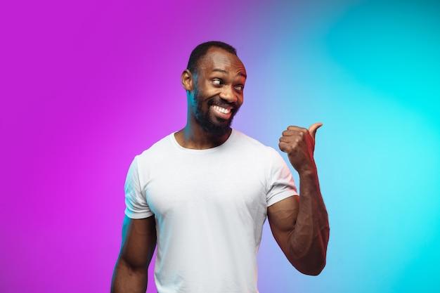 Portrait de jeune homme afro-américain sur fond de studio dégradé en néon