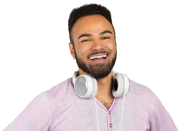 Portrait d'un jeune homme afro américain gai écoutant de la musique avec des écouteurs