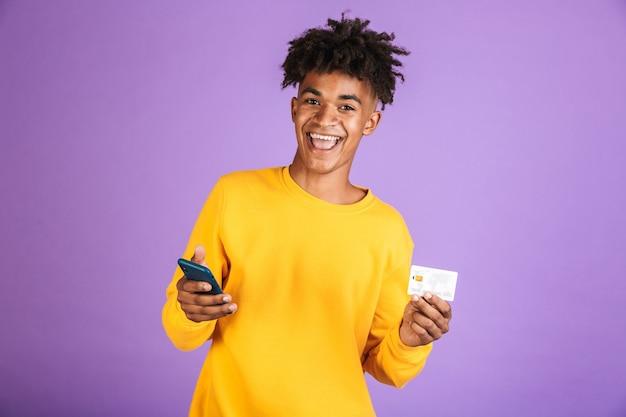 Portrait d'un jeune homme afro-américain heureux en sweat-shirt isolé, criant