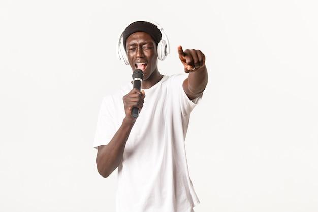 Portrait de jeune homme afro-américain insouciant et cool, effectuant au karaoké, chantant dans le microphone tout en portant des écouteurs