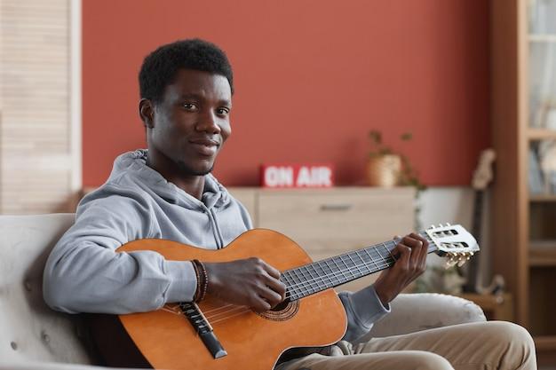 Portrait de jeune homme afro-américain jouant de la guitare acoustique et souriant à la caméra alors qu'il était assis sur le canapé à la maison, copiez l'espace