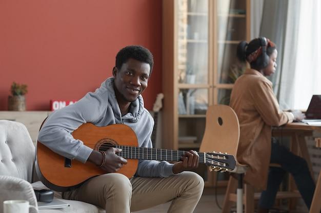 Portrait de jeune homme afro-américain jouant de la guitare acoustique et souriant à la caméra alors qu'il était assis sur le canapé en studio d'enregistrement, espace copie