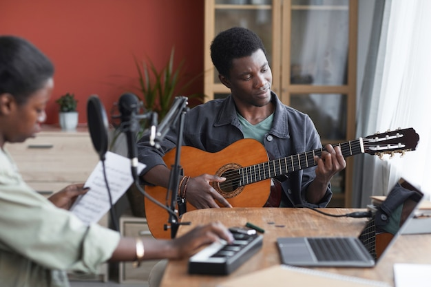 Portrait de jeune homme afro-américain jouant de la guitare acoustique tout en composant de la musique en studio d'enregistrement à domicile, espace copie