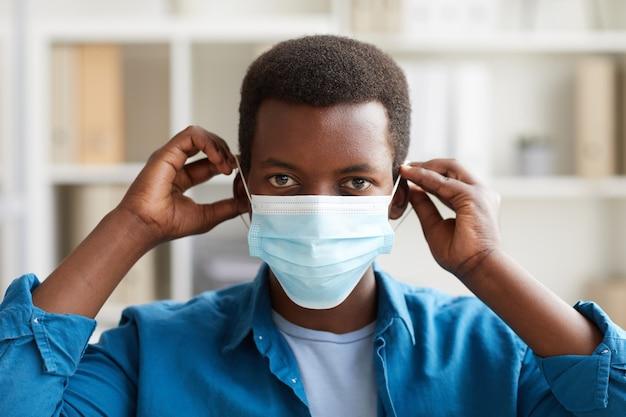 Portrait de jeune homme afro-américain mettant le masque tout en travaillant dans le bureau post pandémie