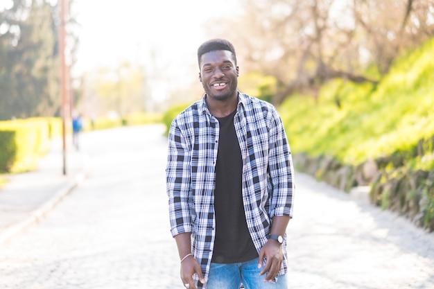 Portrait de jeune homme afro-américain noir debout et souriant à la caméra