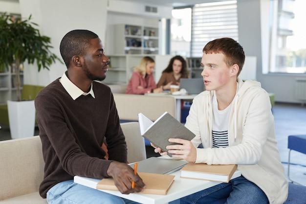 Portrait de jeune homme afro-américain parlant à un ami de l'autre côté de la table tout en étudiant ensemble dans la bibliothèque du collège, préparation aux examens