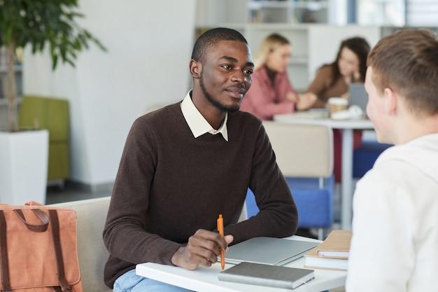 Portrait de jeune homme afro-américain parlant à un ami à travers la table tout en étudiant ensemble dans la bibliothèque du collège,