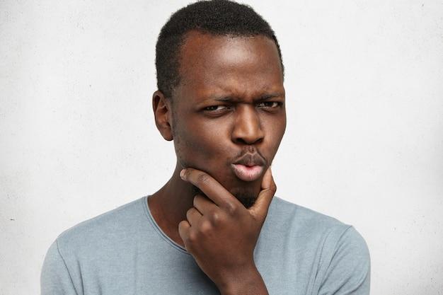 Portrait de jeune homme afro-américain pensif suspect en t-shirt décontracté touchant le visage tout en réfléchissant à quelque chose, en essayant de trouver une solution, ayant une expression perplexe et perplexe