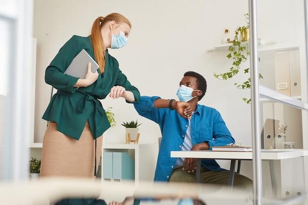 Portrait de jeune homme afro-américain portant un masque facial se cogner les coudes avec une collègue tout en travaillant dans une cabine au bureau post pandémique