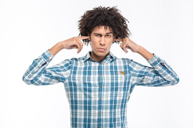 Portrait d'un jeune homme afro-américain sérieux couvrant ses oreilles isolé sur un mur blanc