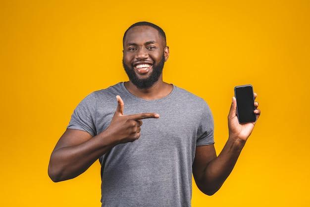 Portrait d'un jeune homme afro-américain souriant habillé en casual isolé, pointant sur un téléphone mobile à écran blanc.