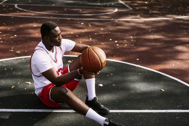 Portrait d'un jeune homme afro-américain tenant un ballon de basket et assis sur un terrain de basket. faites une pause pendant votre entraînement. portrait sportif à la mode.