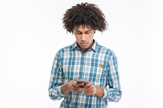 Portrait d'un jeune homme afro-américain utilisant un smartphone isolé sur un mur blanc