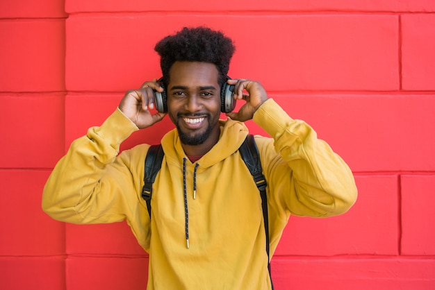 Portrait de jeune homme afro, écouter de la musique avec des écouteurs contre l'espace rouge. concept technologique.