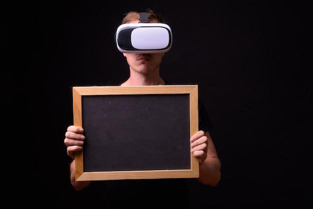 Portrait de jeune homme à l'aide d'un casque de réalité virtuelle et tenant le tableau noir