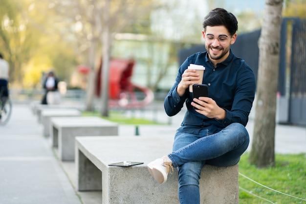 Portrait de jeune homme à l'aide de son téléphone portable et tenant une tasse de café assis sur un banc à l'extérieur. concept urbain.