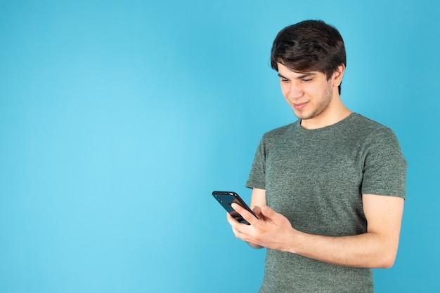 Portrait d'un jeune homme à l'aide d'un téléphone mobile contre le bleu.