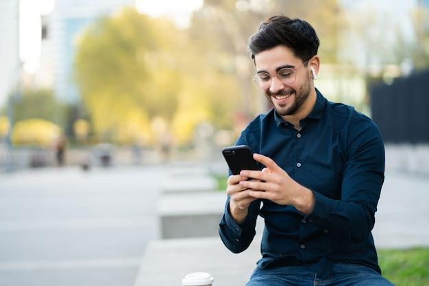 Portrait de jeune homme à l'aide d'un téléphone portable tout en se tenant à l'extérieur