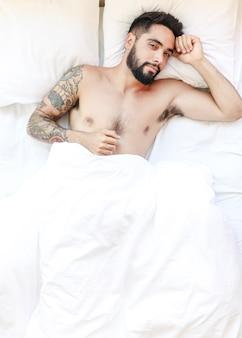 Portrait d'un jeune homme allongé sur un lit