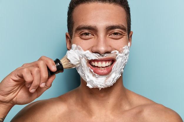 Portrait de jeune homme appliquant la crème à raser