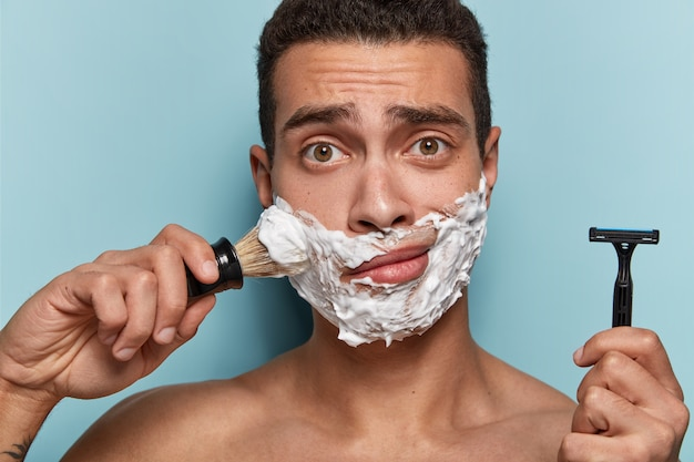 Portrait de jeune homme appliquant de la mousse à raser