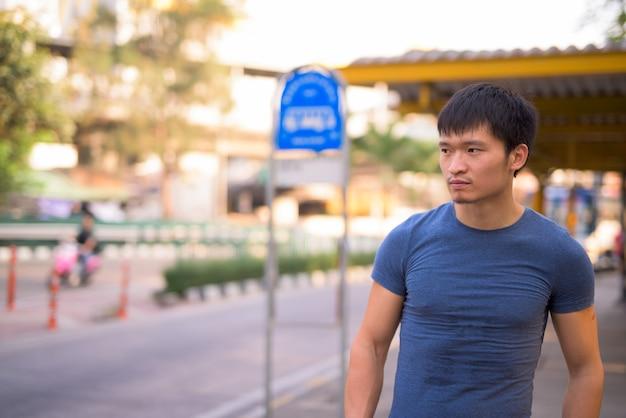 Portrait de jeune homme asiatique à l'arrêt de bus