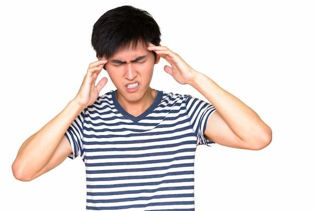 Portrait de jeune homme asiatique ayant des maux de tête isolés contre le mur blanc