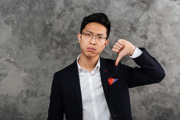 Portrait d'un jeune homme asiatique bouleversé habillé en costume