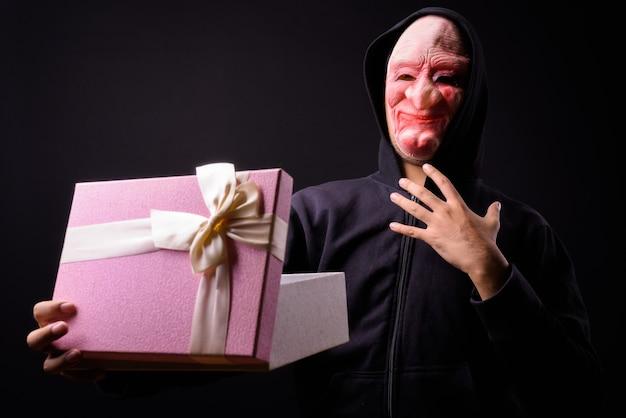 Portrait de jeune homme asiatique avec capuche et masque d'horreur sur fond noir