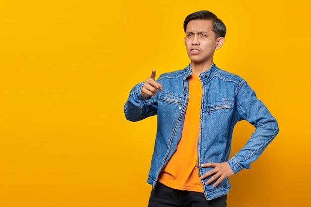Portrait d'un jeune homme asiatique en colère, pointant le doigt vers la caméra avec la bouche ouverte