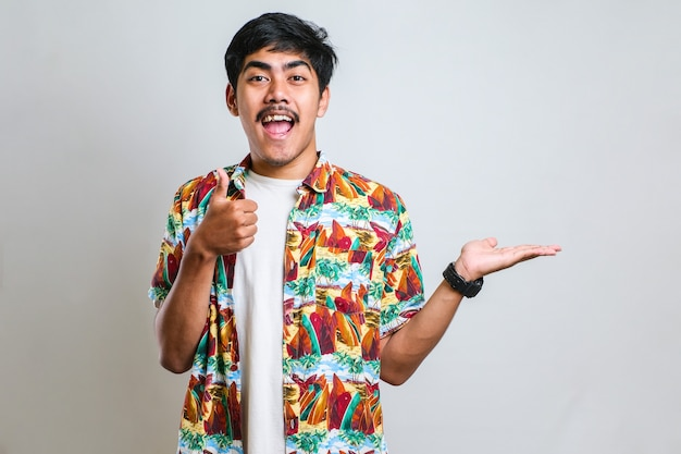 Portrait d'un jeune homme asiatique drôle en t-shirt blanc souriant et montrant quelque chose de son côté, sur fond rouge avec espace pour copie