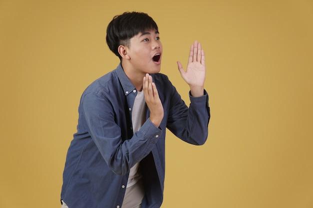 Portrait de jeune homme asiatique excité habillé avec désinvolture avec des cris annonçant main dans la main près de la bouche isolée