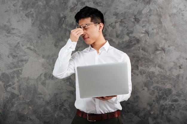 Portrait d'un jeune homme asiatique fatigué vêtu d'une chemise