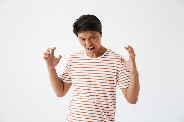 Portrait d'un jeune homme asiatique furieux hurlant