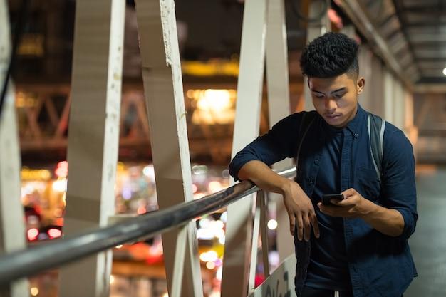 Portrait de jeune homme asiatique sur la passerelle dans la ville pendant la nuit
