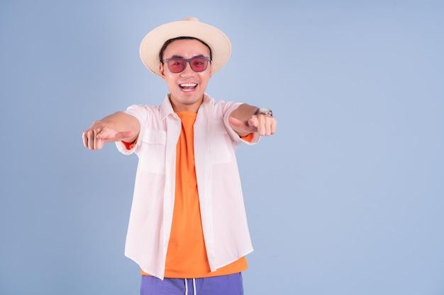 Portrait de jeune homme asiatique portant des vêtements d'été sur fond bleu