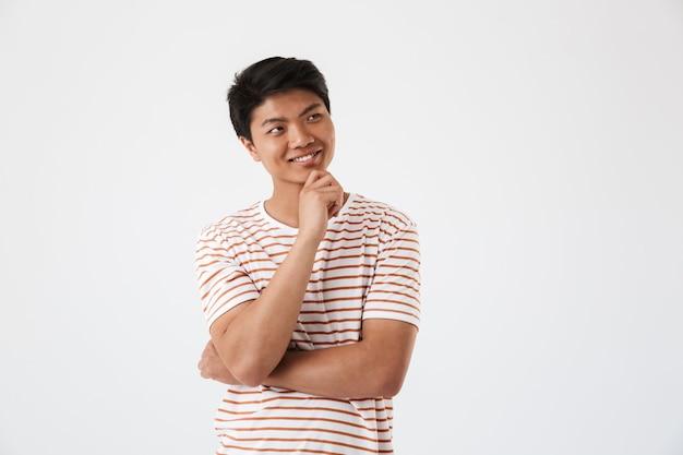 Portrait d'un jeune homme asiatique songeur souriant