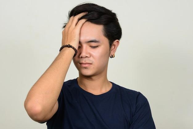 Portrait de jeune homme asiatique stressé ayant des maux de tête