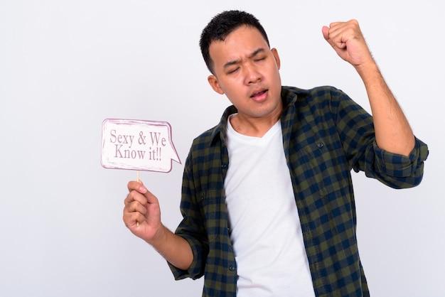 Portrait de jeune homme asiatique tenant une pancarte en papier avec le poing levé