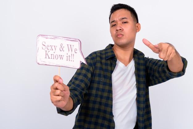 Portrait de jeune homme asiatique tenant une pancarte papier et pointant vers la caméra
