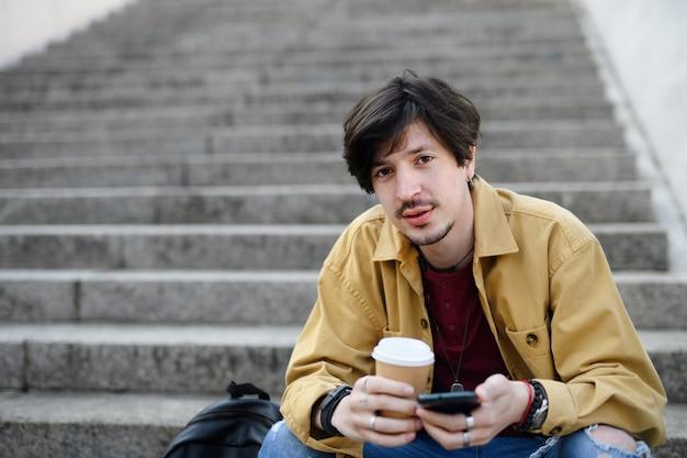Portrait de jeune homme assis sur un escalier à l'extérieur de la ville, à l'aide de smartphone.