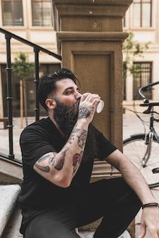Portrait d'un jeune homme assis sur des marches buvant du café