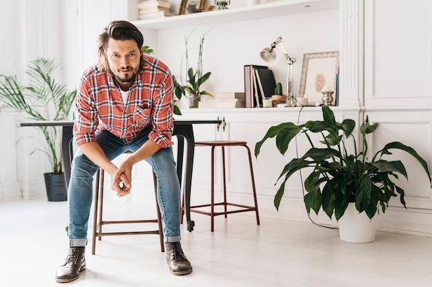 Portrait de jeune homme assis sur un tabouret en regardant la caméra