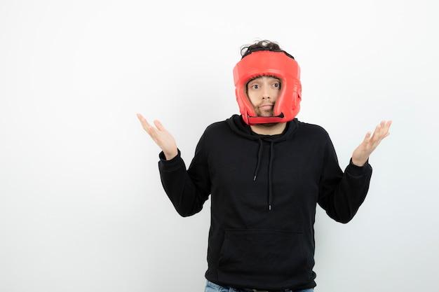 Portrait de jeune homme athlétique au chapeau de boxe rouge debout.