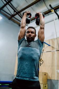 Portrait de jeune homme athlétique faisant de l'exercice avec kettlebel crossfit au gymnase. crossfit, sport et concept de mode de vie sain.