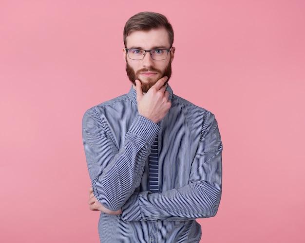 Portrait de jeune homme attrayant à la barbe rousse avec des lunettes et une chemise rayée, touche son menton, regarde pensivement la caméra avec une expression calme sur son visage se dresse sur fond rose.
