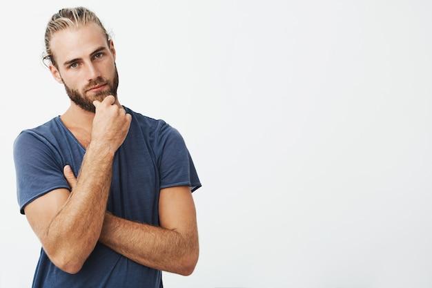 Portrait de jeune homme attrayant avec une coiffure élégante tenant la main sur le menton avec une expression réfléchie