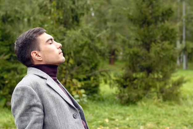 Portrait de jeune homme attrayant avec manteau gris, respirant l'air frais de l'automne dans le parc