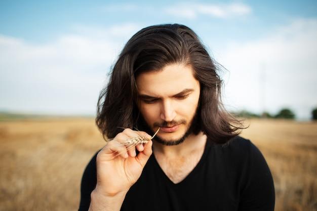 Portrait de jeune homme aux cheveux longs et épi de blé dans la bouche.