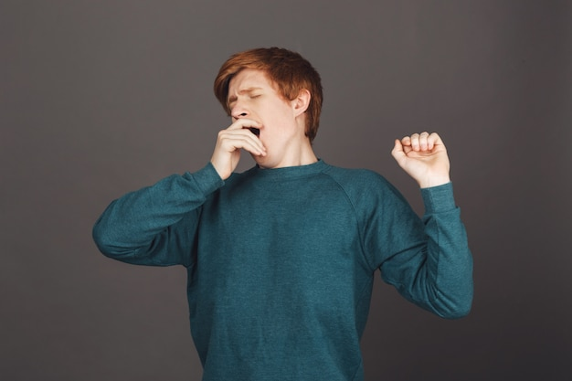 Portrait de jeune homme aux cheveux roux aux cheveux courts en vert sweatshort cothing bouche avec la main